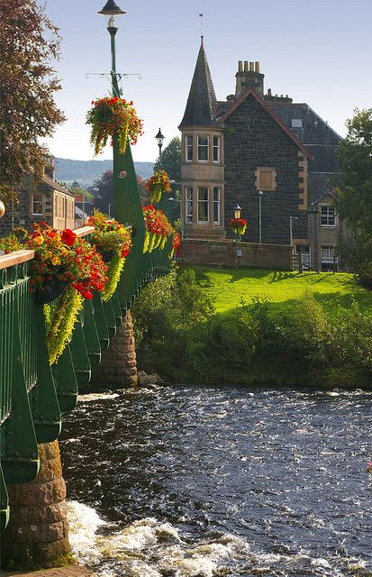 The River Earn flows underneath a flower decorated bridge in Comrie, Scotland